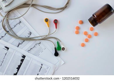 Device of holter monitoring and pills on white background. Concept of diagnosis and treatment of cardiovascular diseases.