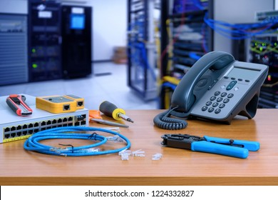 device for network system on table. network gigabit switch, crimping pliers, tester tool and IP Telephone and blur data center room background