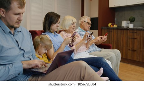 Devices addicted family use tablet, mobile phones sit on sofa at home. Senior couple, mom, dad and child girl obsessed with gadgets overuse social media, people internet technology dependence concept