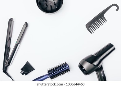 Devices and tools for hair styling on white background with blank space in center, flat lay. Top view of table with professional hair dryer, nozzles, straightener and combs.