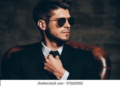 Devil is in details.Portrait of young handsome man in suit adjusting his tie and looking away while sitting in leather chair against dark grey background