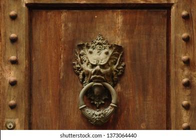 Devil Door knocker On Wooden Gate