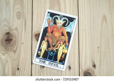 The Devil of Tarot cards on wooden background