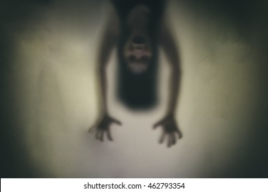 Devil woman hanging upside down, pretending to haunt. Concept blur With noise and dirt