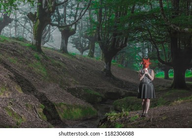 The devil in the woods. A woman with a papercraft mask