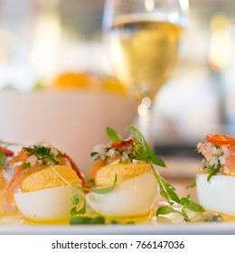 Deviled egg appetizers garnished with smoked fish and fresh herbs. Close up focus with blurred wine glass in the background. Party food.