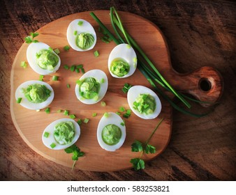 Deviled eggs appetizer with avocado on cutting board. Top view.