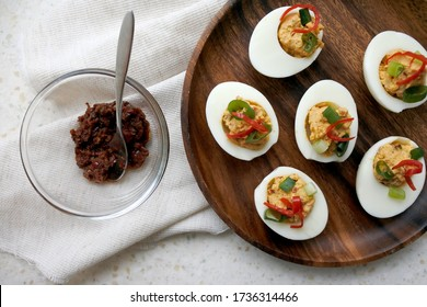 Deviled eggs with Chinese hot sauce, chilis and scallions. Spicy hard boiled egg appetizer. Stuffed eggs on a wooden plate. Light background. Close-up. Free space to place text.