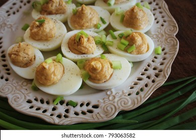 Deviled eggs with cod livers with leek on white plate. Rustic wooden table. Top view
