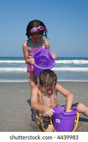 Devious sister sneaks up on brother and dumps a bucket of water on his head.