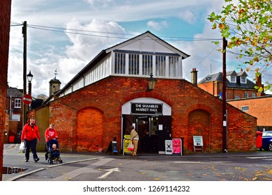 Devizes, Wiltshire / England - 11/4/2017:A couple & young child in pushchair walk past the rear of the historic Shambles Market Hall in  Devizes.