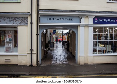 """Devizes Wiltshire UK March 05 2020 An archway between 2 shops with the title """"Old Swan Yard"""" above it, with a flagstone path to small shops in the Wiltshire town of Devizes"""