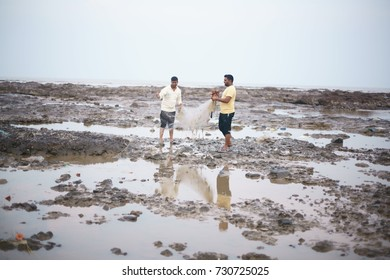 DEVKA BEACH, DAMAN, INDIA - OCTOBER 8, 2017: A couple of fishermen are seen pulling out the nets early morning during low tide to see what they have caught, at the DEVKA BEACH.