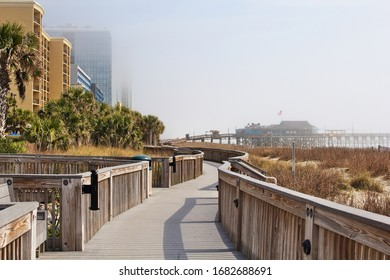 A devoid of people boardwalk near the end of the board walk at Myrtle Beach on a foggy morning during spring break 2020 amid the Covid-19 epidemic.