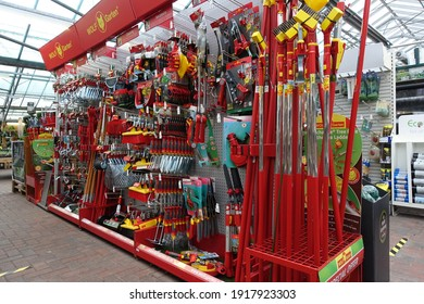 Devon England. February 2021. Gardening equipment and tools on a display rack Hoes, rakes, trowels, spades, forks. Red handles. Colourful selection.