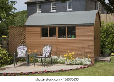 DEVON ENGLAND UK - JUNE 2016 - A barn style garden shed with a small patio and chairs