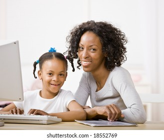 Devoted mother helping daughter do homework on computer