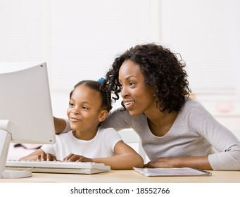 Devoted mother helping girl do homework on computer