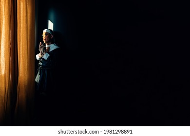 devoted nun prays in the light of a convent window. crossdressing drag queen, religion, identity. black copy space background