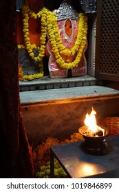 Devotional flame before marigold decorated image of Hanuman outside Sindhi Temple,  Jaipur, Rajasthan, India