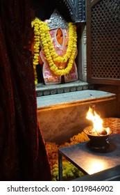Devotional flame before marigold decorated image of Hanuman outside Sindhi Temple,  Jaipur, Rajasthan, India