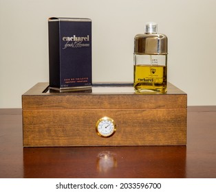 Brasília, Df, Brazil, August 30, 2021. Cacharel Pour Homme male perfume on a wooden box to store cigars with humidity control on a rustic wooden table and white background.
