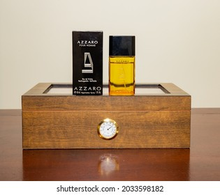 Brasília, Df, Brazil, August 30, 2021. Azzaro pour homme male perfume on a wooden box to store cigars with humidity control on a rustic wooden table on a white background.