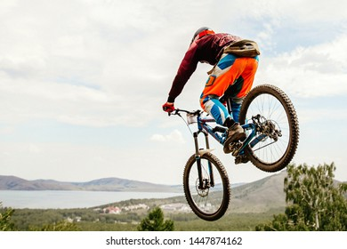 dh rider jumping and flight downhill racing in background forest and lake