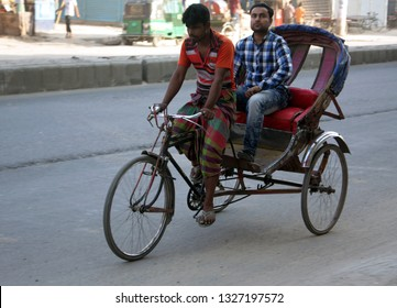 Dhaka, Bangladesh - 03 09 2018: A Rickshaw Puller transporting customer. Cycle rickshaws (riksha) are popular modes of transport in many countries for short distances. Poor people work to earn money