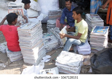 Dhaka, Bangladesh - 03 11 2018: Group of men sitting and reviewing pile of old newspapers & magazines. Eco-friendly way to get rid of old papers is to recycle for cleaner and safer environment