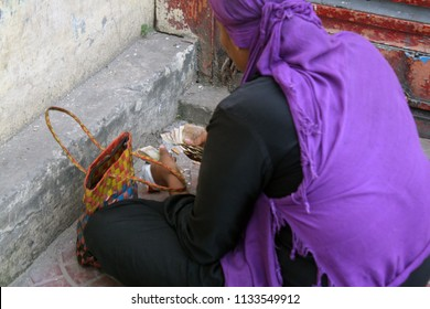 Dhaka, Bangladesh - 07 13 2018: Poor homeless woman counting money. Street woman begging to buy food. Woman of the world need education, shelter, financial aid from Government, NGO, human org