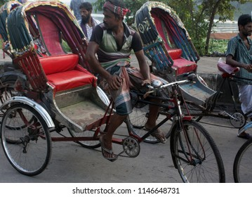 Dhaka, Bangladesh - 07 28 2018: A Rickshaw Puller waiting for customers. Cycle rickshaws (riksha) are popular modes of transport in many countries for short distances. Poor people work to earn money