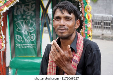 Dhaka, Bangladesh - 09 04 2018: Rickshaw Puller smoking in public. Middle aged poor smoking cigarette in local street, working to earn money. Causes of many diseases lung cancer, heart attack, COPD