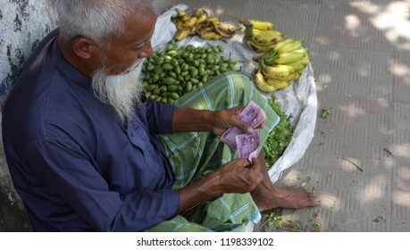 Dhaka, Bangladesh - 09 18 2018: Asian old man with white beard sale fruit in street. Middle aged poor man working in local market to earn money. Government, NGO help needed common people world