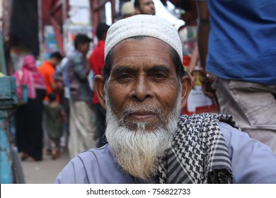 Dhaka, Bangladesh - 10 29 2016: Asian Muslim male old man with white beard and tupi. Middle aged poor man working in local shop market to earn money. Government, NGO help needed common people world