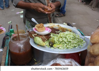 Dhaka, Bangladesh - 10 29 2016: Delicious deep fried poori (puri) served with spicy chutney & fresh salad. Popular street food in local market. Mostly young boys & girls eat puri in food stalls.