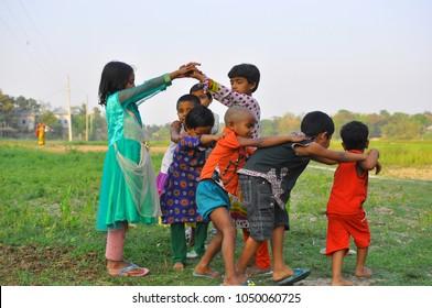 Dhaka, Bangladesh, 17 February 2018: An image of children playing in the open field of a rural area near Dhaka, Bangladesh.