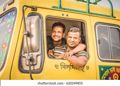 DHAKA, BANGLADESH - APRIL 09, 2017: Two truck drivers hugging eachother and hanging out of their vehicle window