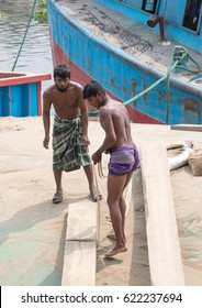DHAKA, BANGLADESH - APRIL 16, 2017: Two handsome and muscled and very fit workers wearing a lunghi skirt