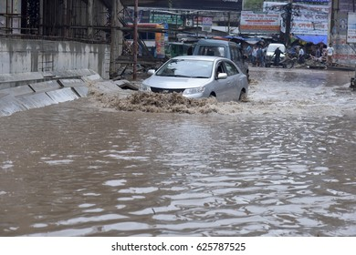 DHAKA, BANGLADESH - APRIL 22, 2017: Vehicles try driving through a flooded street in Dhaka. Water-logging has become a perennial problem for the residents of Dhaka city Bangladesh on April 14, 2017.