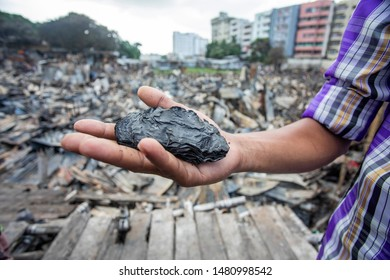 Dhaka, Bangladesh- August 17, 2019:  Mohammad Ismail, a dweller of the slum shows his burned bundle of five-hundred-taka bill by last night fire in Chalantika area at Mirpur.