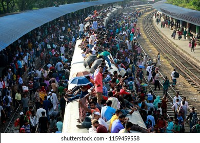 Dhaka, Bangladesh - August 19, 2018: Bangladeshi people try to climb on to the roof of an overcrowded train as they return to their hometowns ahead of the Muslim holiday of Eid al-Fitr, in Dhaka.