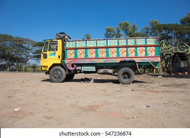 DHAKA, BANGLADESH - DECEMBER 10, 2016: Colorful yellow cargo truck under a summer blue sky with rich decorative paintings, typical for the trucks in Bangladesh, Pakistan and India.