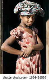 DHAKA, BANGLADESH - DECEMBER 25, 2020: Portrait of a young african looking girl in a small village wearing old clothes at her head standing in the door opening