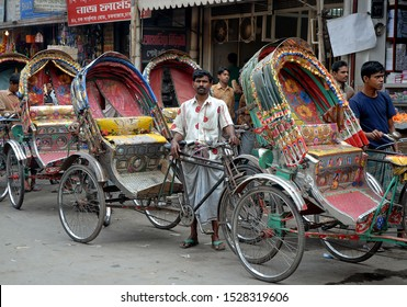 Dhaka / Bangladesh - Feb 14 2006: A rickshaw driver in Dhaka, Bangladesh. A line of rickshaws with drivers waiting for business. Local transport, Dhaka, Bangladesh.