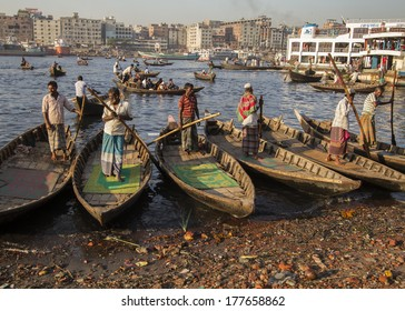 DHAKA, BANGLADESH - FEBRUARY 15, 2013: Men stand in their boats, waiting for clients to take across the Buriganga River.  Dozens of craft ply the waters of the river carrying passengers and cargo.