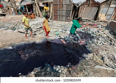 DHAKA, BANGLADESH - FEBRUARY 16, 2018: A Bangladeshi girl crosses a canal full with toxic chemical in Dhaka, Bangladesh. Toxic waste from industries has turned water into red, Dhaka, Bangladesh.