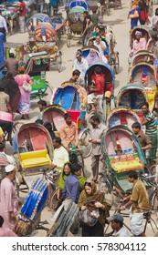 "DHAKA, BANGLADESH - FEBRUARY 22, 2014: Rickshaws transport passengers in Dhaka, Bangladesh. About 500 000 rickshaws daily cycle in Dhaka, nicknamed ""the rickshaws capital of the world""."