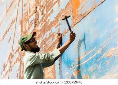 Dhaka, Bangladesh, February 24 2017: A worker at a shipyard in Dhaka Bangladesh beats the rust from the hull with a hammer