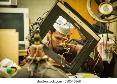DHAKA, BANGLADESH - JANUARY 06, 2017: Primitive television repair shop where a technician is trying to repair a TV set